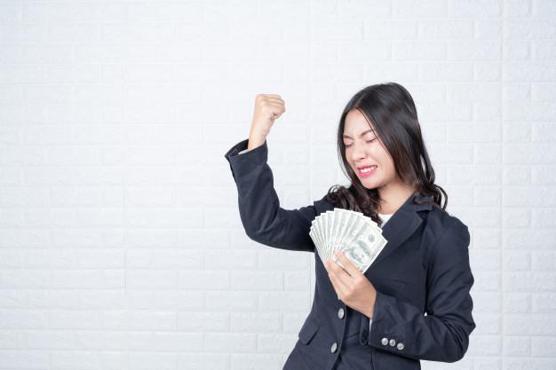 Ilustrasi - Wanita memegang uang. Foto: Freepik