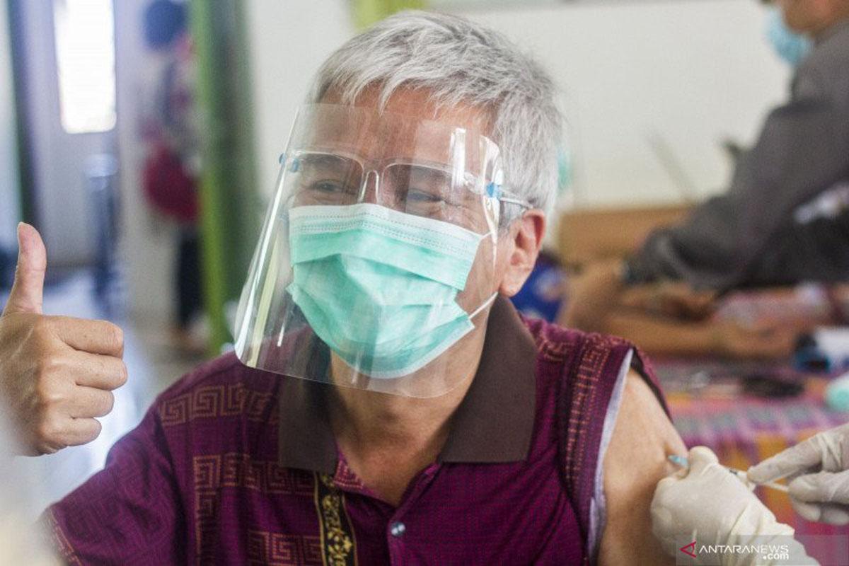 Seorang warga lansia (lanjut usia) mengangkat jempol saat menjalani penyuntikkan vaksin COVID-19. (Foto: ANTARA FOTO/BAYU PRATAMA S)
