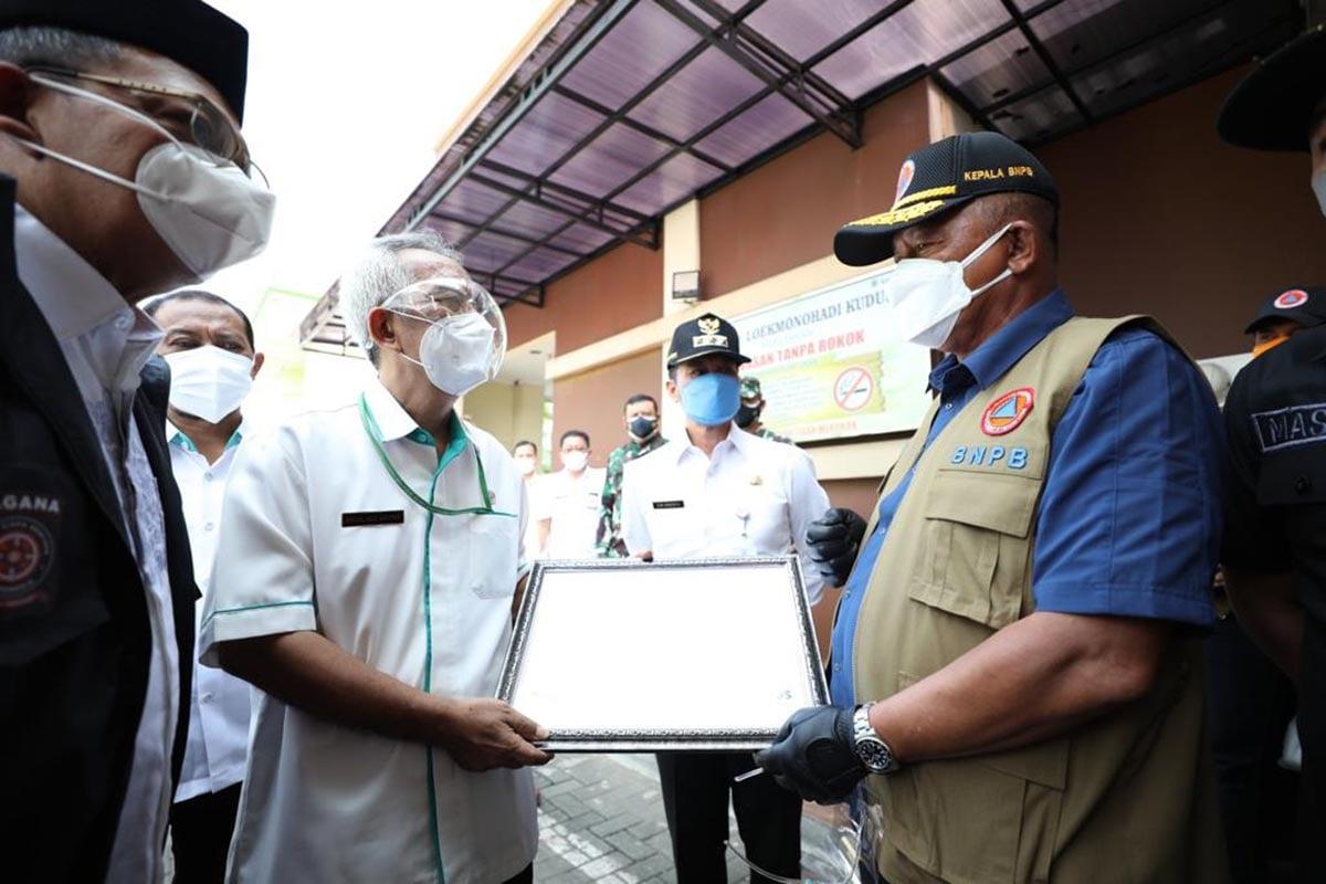 Kepala BNPB sekaligus Ketua Satgas Penanganan COVID-19 Ganip Warsito (kanan) menyerahkan bantuan secara simbolis kepada Pemerintah Kabupaten Kudus, Kamis (3/6).(Foto: Humas BNPB)