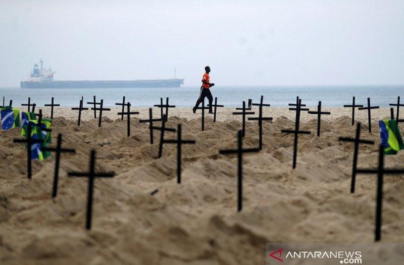 Ratusan makam yang digali aktivis LSM Rio de Paz di pantai Copacabana, menyimbolkan banyak korban meninggal dunia akibat Covid-19, di Rio de Janeiro, Brazil, Kamis (11/6/2020). Foto: Reuters/Pilar Olivares/aww/cfo.