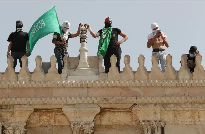 Beberapa warga Palestina mengibarkan bendera Hamas di atap Masjid Al-Aqsa pada 10 Mei 2021 silam (Foto: AMMAR AWAD/REUTERS)