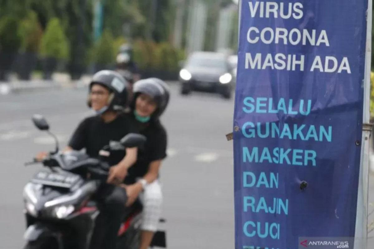 Ilustrasi - Pengendara sepeda motor tanpa menggunakan masker melintas di dekat spanduk sosialisasi penerapan protokol kesehatan di Kota Kediri, Jawa Timur, Jumat (25/12/2020). (ANTARA/Prasetia Fauzani)