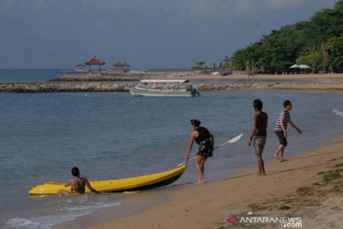 Wisatawan menikmati suasana saat mengunjungi di Pantai Sindhu, Sanur, Denpasar, Bali, Rabu (9/6/2021). (Foto: Antara/Nyoman Hendra/2021)