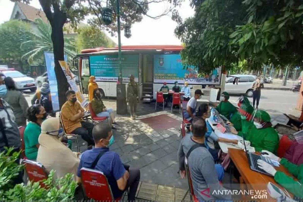 Petugas medis dari Dinas Kesehatan Kota Surakarta saat melayani program vaksinasi dengan mobil keliling di depan Pasar Ngarsopuro Banjasari Solo, Selasa (15/6/2021). (FOTO: ANTARA/Bambang Dwi Marwoto)