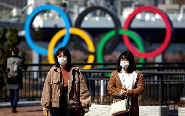 Orang mengenakan masker pelindung di depan cincin raksasa Olimpiade di area Olimpiaden dei Odaiba Marine Park di Tokyo, Jepang, 27 Februari 2020. Foto: Antara/Reuters/Athit Perawongmetha.