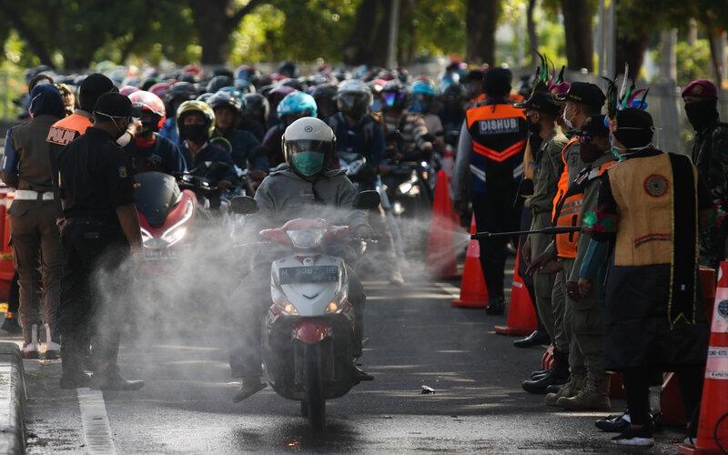 Petugas menyemprotkan larutan disinfektan ke kendaraan bermotor yang memasuki Surabaya di pintu keluar Jembatan Suramadu, Surabaya, Jawa Timur, Senin (20/4/2020). -Foto: Antara/Didik Suhartono