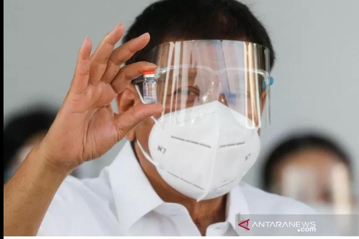 Presiden Filipina Rodrigo Duterte memegang sebotol vaksin virus corona (COVID-19) Sinovac, vaksin COVID-19 pertama yang tiba di negara itu, di Pangkalan Udara Villamor, Kota Pasay, Metro Manila, Filipina, Minggu (28/2/2021). Foto: ANTARA /REUTERS/Eloisa L