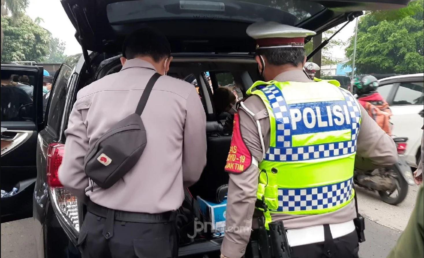 Petugas kepolisian saat memeriksa mobil yang diduga milik simpatisan di depan Pengadilan Negeri Jakarta Timur, Kamis (24/6) (Foto : Kenny Kurnia Putra/JPNN.com)