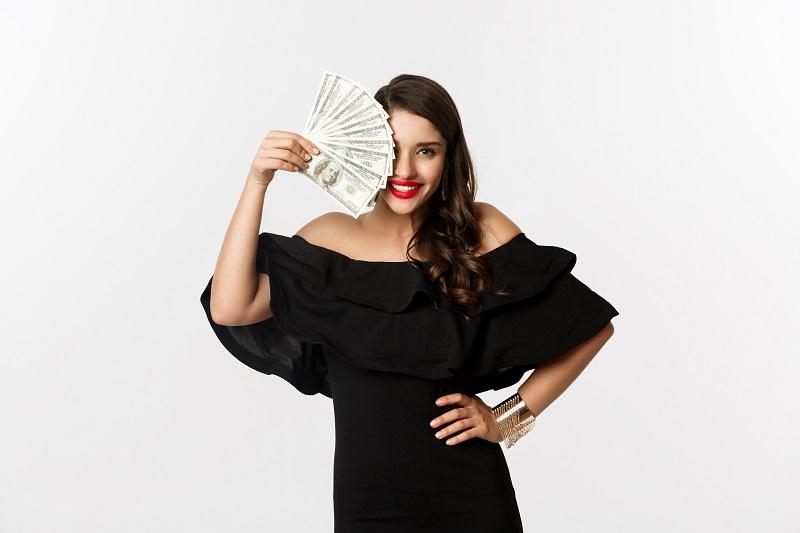 Ilustrasi - wanita memegang uang. Foto: Freepik.