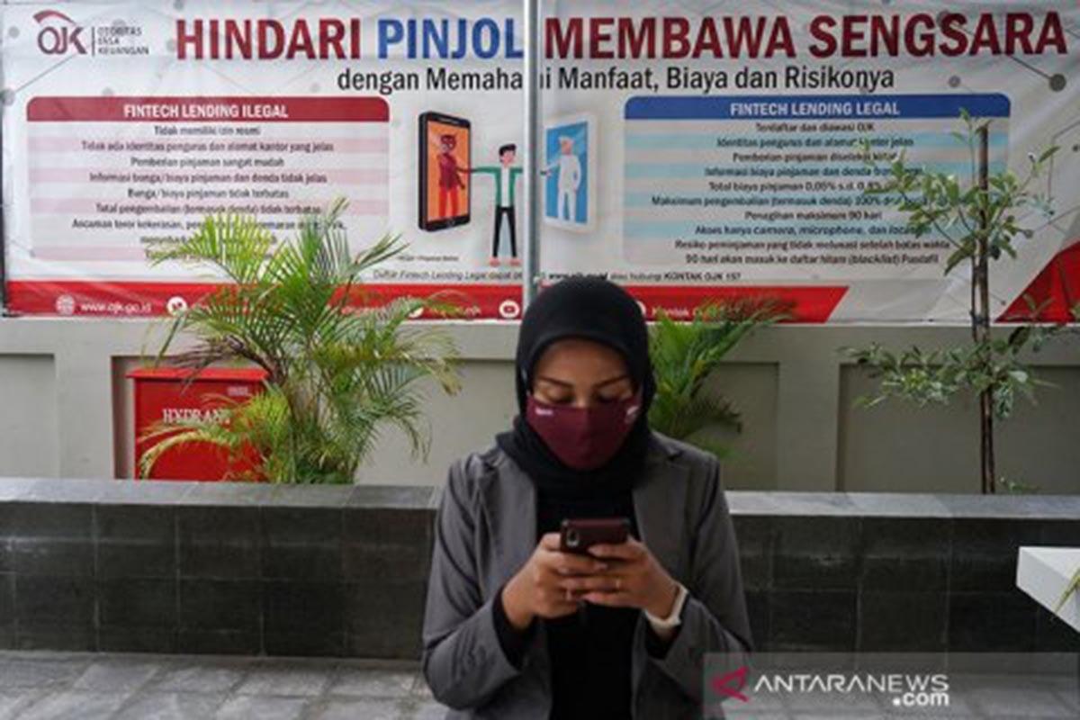 Warga berada di dekat poster edukasi waspada fintech ilegal di kantor Otoritas Jasa Keuangan (OJK) Yogyakarta, Rabu (4/11/2020). (FOTO: ANTARA FOTO/Andreas Fitri Atmoko/foc)