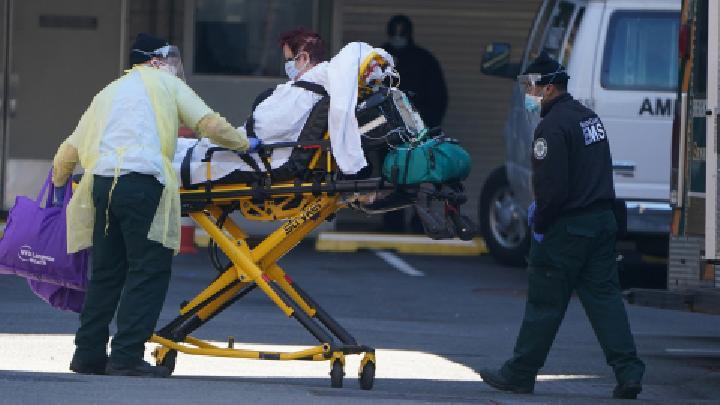 Ilustrasi pasien positif covid-19 dibawa petugas medis menuju ambulans di Manhattan, New York, beberapa waktu lalu. REUTERS/Carlo Allegri