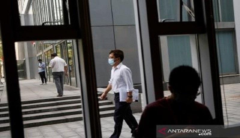 Seorang warga yang memakai masker terlihat melewati Starbucks di Beijing, China. Foto: Antara