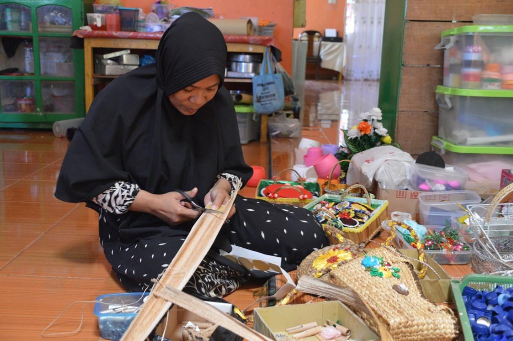 Nining Mantali dan barang bekas yang dikumpulkan untuk dibuat kerajinan bernilai ekonomi. (Foto: AK Pakaya)