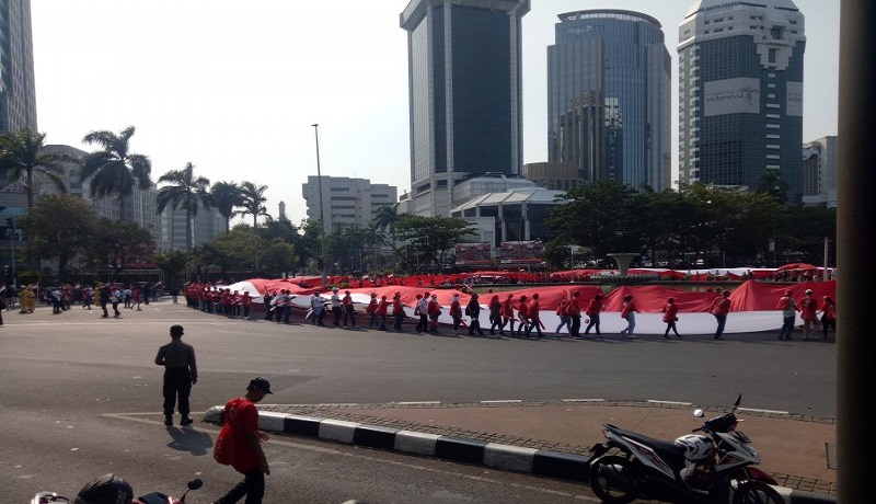 Bendera raksasa sepanjang 200 meter dibentangkan relawan Jokowi-Maruf di Bunderan Patung Kuda, Monas. Foto: Antara