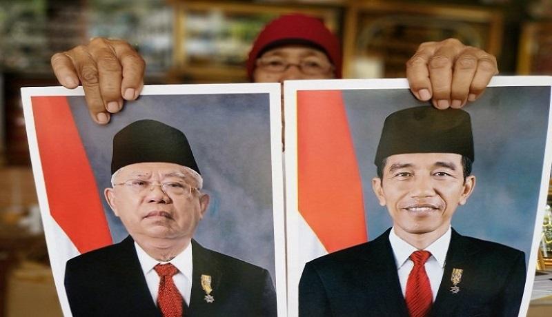 Pedagang bingkai menunjukan foto Jokowi-Mar'uf Amin. Foto: Antara