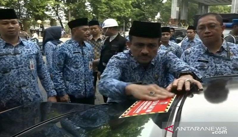 Wali Kota Jakarta Timur, M Anwar, menempel stiker di salah satu kaca mobil milik Aparatur Sipil Negara (ASN) yang belum melunasi pajak kendaraan. Foto: Antara