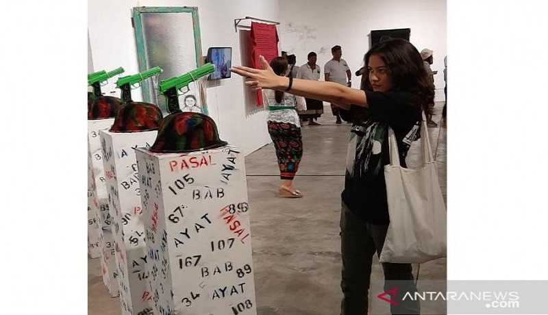 Pengunjung pameran yang tengah asyik melihat sambil memperagakan aksi memegang pistol di depan seni instalasi karya Ketut Putrayasa. Foto: Antara