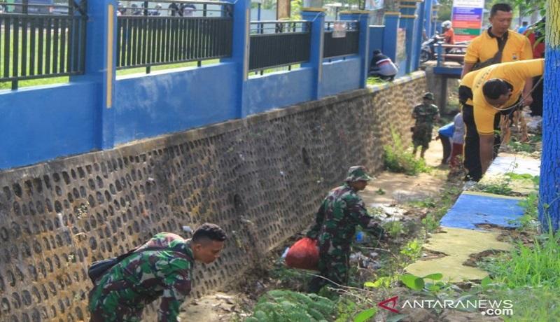 Aksi bersih-bersih sampah plastik prajurit TNI Koramil Pakong bersama polisi dan warga, Jumat (6/12). Foto: Antara
