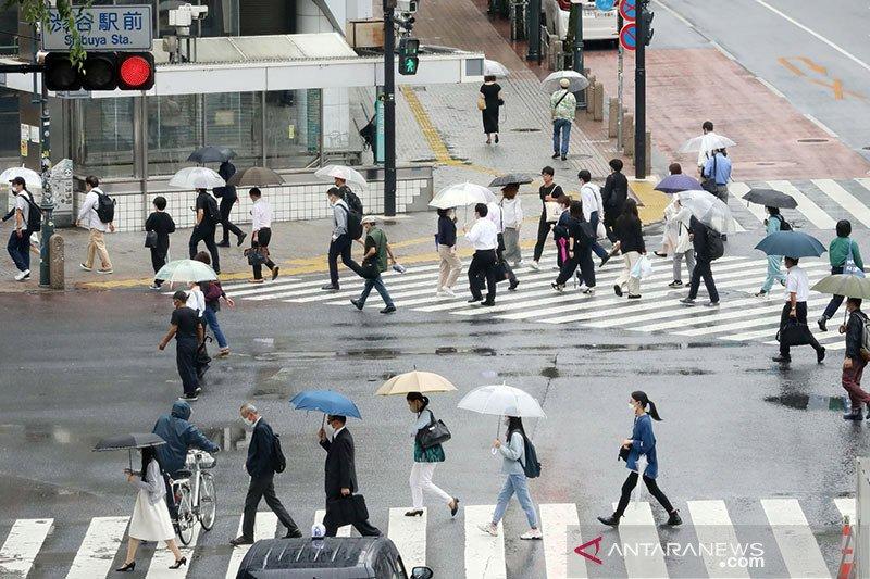 Para warga dengan memakai masker terlihat berjalan di Penyeberangan Shibuya di Shibuya Ward, Tokyo. (Foto: Antara/Reuters/The Yomiuri Shimbun/Ryohei Moriya/nz/cfo/am)