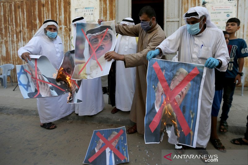 Warga Palestina membakar foto mirip Presiden Amerika Serikat Donald Trump, Perdana Menteri Israel Benjamin Netanyahu dan Raja Bahrain Hamad bin Isa Al Khalifa saat protes atas keputusan Bahrain untuk memulihkan hubungan dengan Israel, di pusat Jalur Gaza,