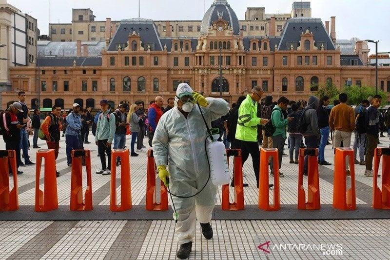 Petugas pembersih menggunakan desinfektan di pintu masuk kereta bawah tanah di Buenos Aires, Argentina, Kamis (19/3/2020). (Foto: Antara/Reuters/Matias Baglietto/am.)