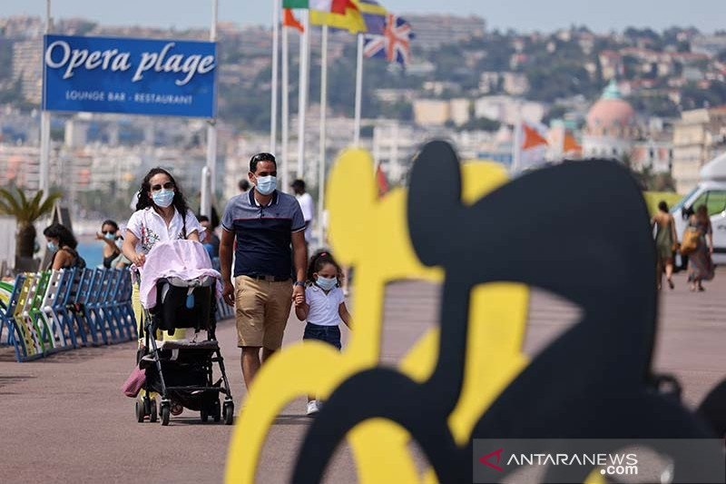 Wisatawan berjalan melintasi logo balap sepeda Tour De France edisi ke-107, di French Riviera, Nice, Prancis (26/8/) di tengah kehawatiran soal wabah virus corona (COVID-19). (Foto: Antara/AFP/Kenzo Tribouillard/aa.)