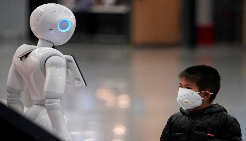 Seorang anak lelaki memperhatikan robot sambil memakai masker di Bandara Internasional Pudong di Shanghai, China. Foto: Antara