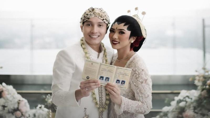 Isyana dan Rayhan menunjukkan buku nikah (foto: SC IG @thebridestory)