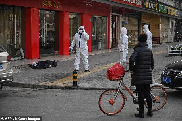 Petugas kesehatan menangangi warga Wuhan yang meninggal di jalan karena terjangkit virus Corona. Foto: AFP via Getty Images