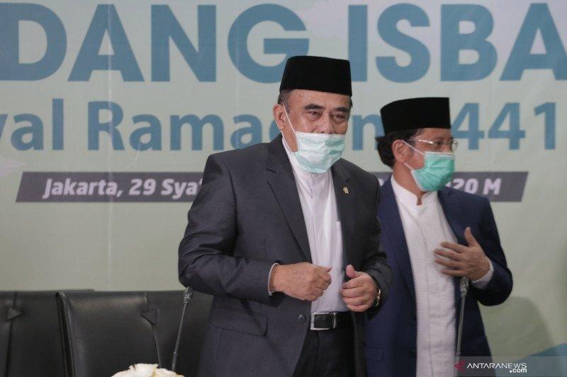 Menteri Agama Fahrur Rozi (kiri) didampingi Dirjen Bimas Islam Kamaruddin Amin (kanan) berdiri usai menyampaikan hasil Sidang Isbat penentuan awal Ramadhan 1441 Hijriah dari Kantor Kementerian Agama, Jakarta, Kamis (23/4/2020). Pemerintah mengumumkan 1 Ra