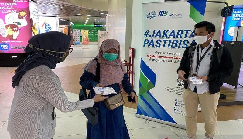 Petugas memberikan masker gratis kepada penumpang MRT Jakarta. Foto: Antara
