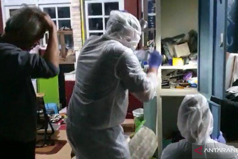 Polisi pakai APD lengkat saat menggeledah rumah Tio Pakusadewo. Foto: Antara