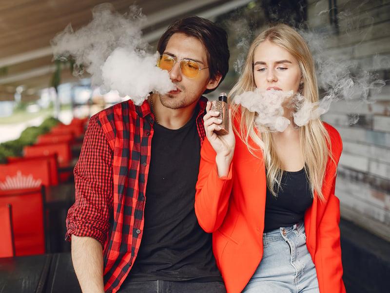 Pria dan wanita mengisap rokok elektrik alias vape. Foto: Prostooleh/Elementsenvato