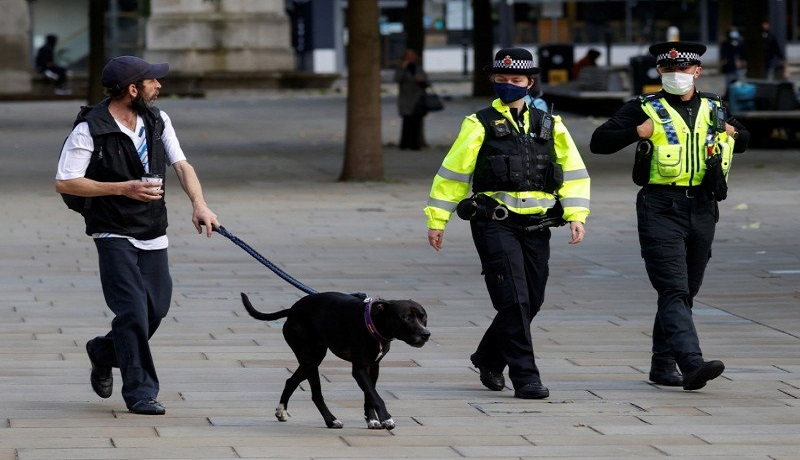 Polisi memakai masker sambil membawa anjing, ditengah wabah penyakit virus corona. FOTO: Phil Noble/Reuters/Antara
