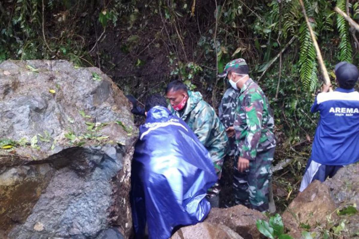 Petugas mengevakuasi pengendara sepeda motor yang tertimpa batu saat terjadi gempa Malang di Jalur Piket Nol, Kabupaten Lumajang, Jawa Timur, Sabtu (10/4/2021). Foto: ANTARA/HO-BPBD Lumajang