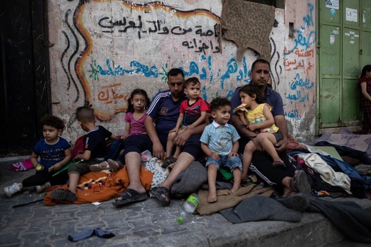 Keluarga Palestina di luar rumahnya yang diserang Israel. Foto: AP Photo/Khalil Hamra