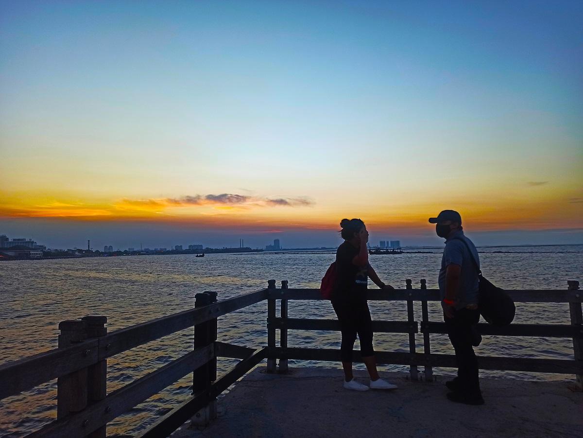 Sepasang kekasih menikmati matahari terbenam di Pantai Ancol (Foto: Andi Ristanto/GenPI.co)