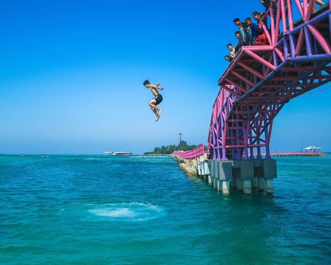 Wisatawan melompat ke laut dari atas Jembatan Cinta, Pulau Tidung (Foto: Instagram/@pulautidung_jakarta)