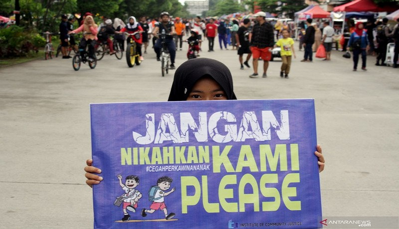 Seorang anak membawa poster saat aksi peringatan Hari Perempuan Internasional. FOTO: Antara