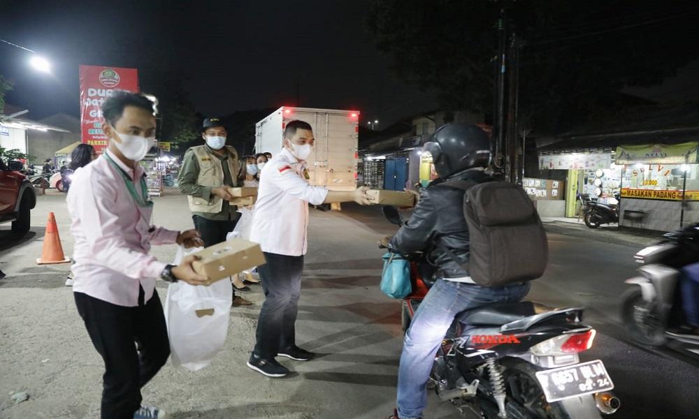 Angkatan Muda Kabah (AMK) bagi-bagi nasi kotak ke masyarakat di Bekasi, Jawa Barat. FOTO: GenPI.