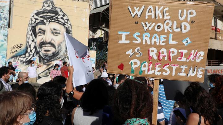 Orang-orang memegang tanda saat ikuti aksi solidaritas untuk Palestina di kamp pengungsi Mar Elias di Beirut, Lebanon, 11 Mei 2021. Aksi mereka tersebut untuk mendukung rakyat Palestina dan mengecam kekerasan yang dilakukan oleh militer Israel ke warga Pa