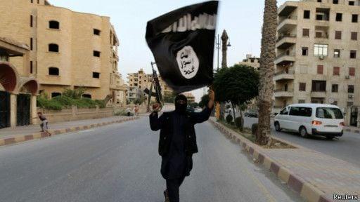 Seorang pejuang membawa senjata dan bendera ISIS. Foto: Reuters.