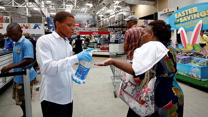 Petugas memberikan cairan hand sanitizer pada warga yang mengantre untuk membeli bahan makanan di supermarket, menjelang diberlakukannya lockdown selama 21 hari, sebagai upaya mencegah penyebaran Virus Corona di Johannesburg, Afrika Selatan, 24 Maret 2020