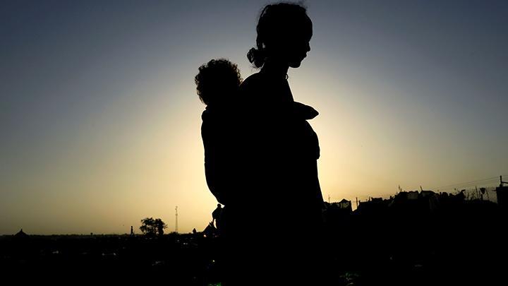 Seorang wanita Ethiopia yang melarikan diri dari pertempuran yang sedang berlangsung di wilayah Tigray, membawa anaknya di dekat sungai Setit di perbatasan Sudan-Ethiopia di desa Hamdayet di negara bagian Kassala timur, Sudan 22 November 2020. Ribuan oran