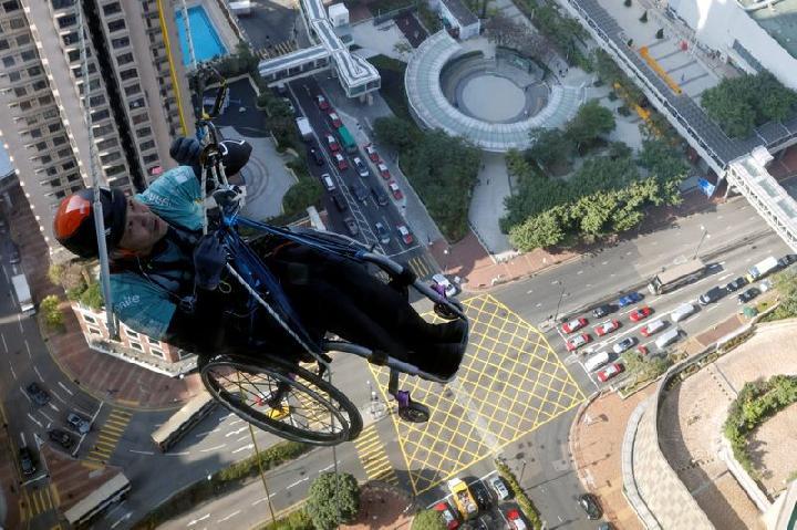 Lai Chi-wai, seorang pendaki yang lumpuh, mencoba memanjat Nina Tower setinggi 320 meter hanya dengan menggunakan kekuatan tubuh bagian atasnya, di Hong Kong, Cina 16 Januari 2021. Dalam upaya ini, Lai menyelesaikan 250 meter saat dia menghadapi angin ken