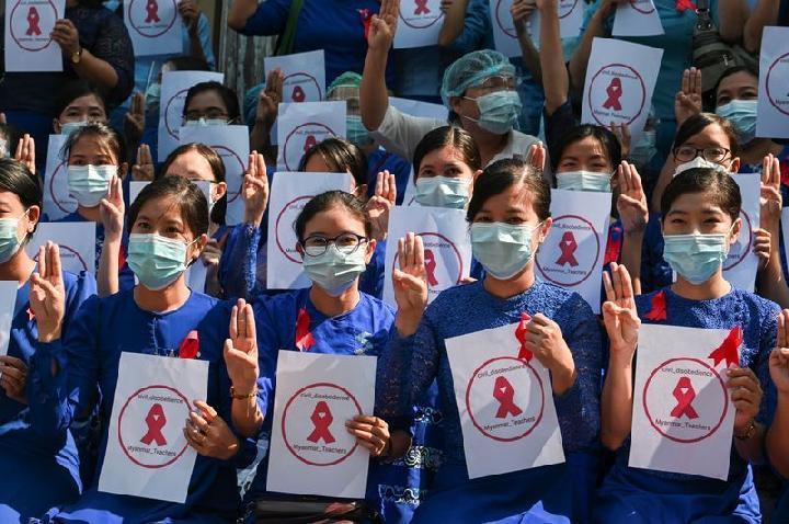 Guru dari Yangon University of Education mengenakan pita merah dan berpose dengan salam tiga jari saat mereka ambil bagian dalam demonstrasi menentang kudeta militer di Yangon, Myanmar, 5 Februari 2021. Foto: Reuters.