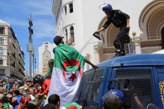 Seorang petugas polisi menyemprotkan gas air mata ke pengunjuk rasa anti-pemerintah di Aljir, Aljazair 17 Mei 2019. Foto: Reuters/Ramzi Boudina/ar.