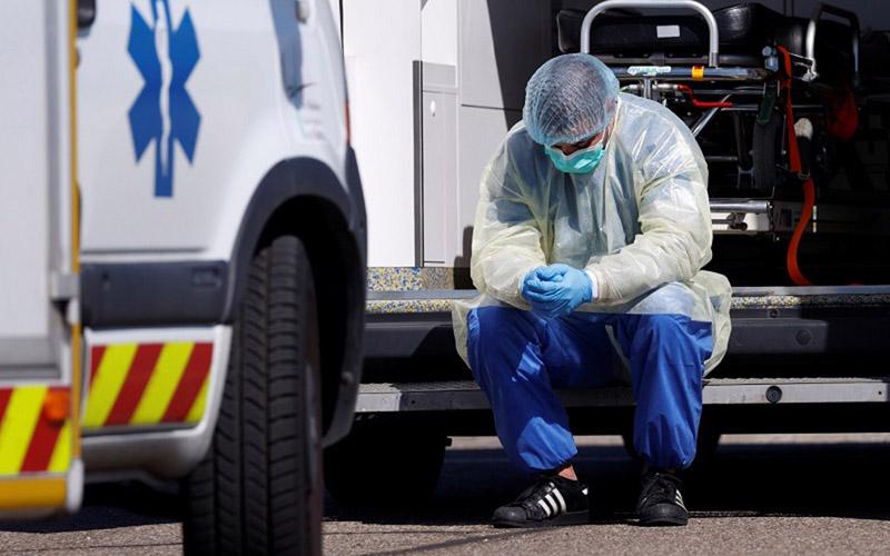 Ilustrasi-Tenaga medis tengah tertunduk di halaman rumah sakit. Foto: Reuters.
