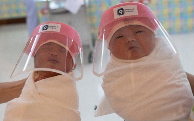 Ilustrasi-Dua bayi yang baru lahir menggunakan pelindung wajah di tengah pandemi virus corona. Foto: Antara/Reuters.