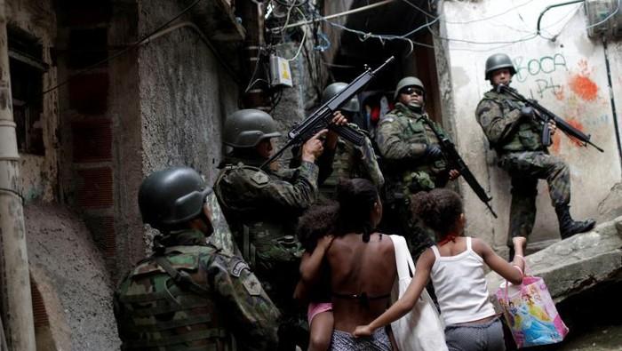 Tentara mengambil posisi dalam operasi setelah terjadi bentrokan antara kelompok narkoba di daerah kumuh Rocinha di Rio de Janeiro, Brasil. Foto: Dok Reuters/Ricardo Moraes.